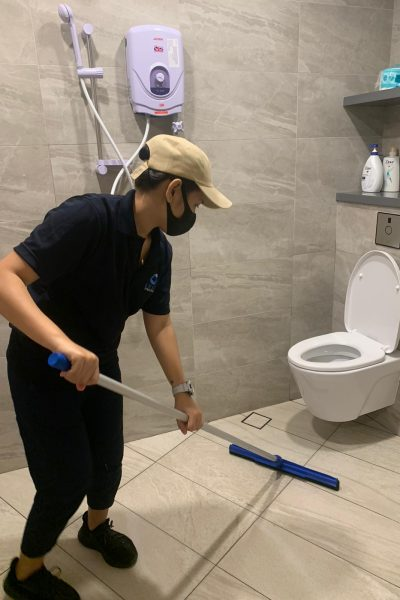 cleaner using toilet squeegee to dry out the toilet floor after washing