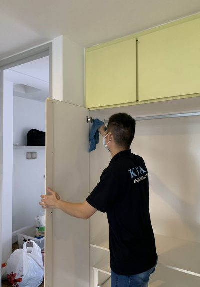 male cleaner wiping the interior of wardrobe